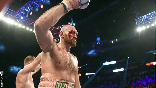 A bloodied Tyson Fury raises his glove at the end of the fight
