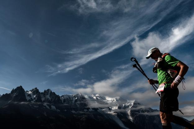 An ultra trailer walks past Mont Blanc at La Flegere path near Chamonix