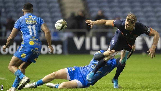 Edinburgh wing Duhan van der Merwe off-loads the ball against Dragons