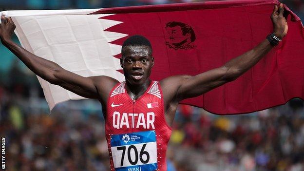 Abdalelah Haroun hold aloft a Qatari flag