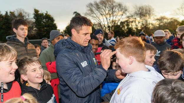 Dan Carter signs an autograph on a child's forehead