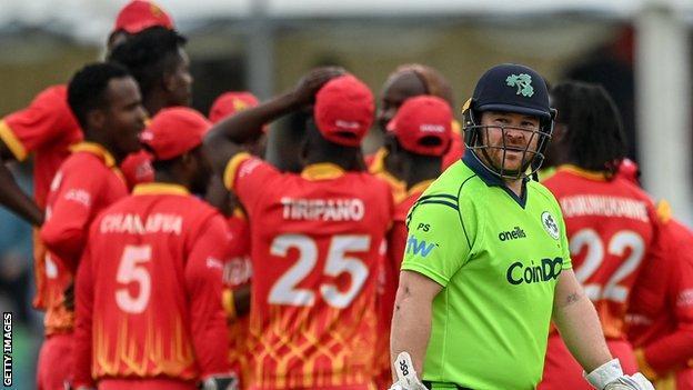 A dejected Paul Stirling walks off as Zimbabwe celebrate dismissing the Irish opener