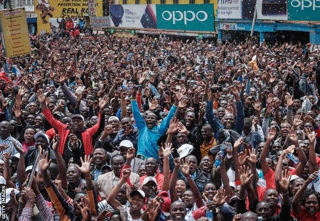 Kenyans watch a big screen on October 12, 2019, in Nairobi as they celebrate Kenya's Eliud Kipchoge victory. - Kenya's Eliud Kipchoge, on October 12, 2019, made history, busting the mythical two-hour barrier for the marathon on a specially prepared course in a huge Vienna park. With an unofficial time of 1hr 59min 40.2sec, the Olympic champion became the first ever to run a marathon in under two hours in the Prater park with the course readied to make it as even as possible. (Photo by Yasuyoshi CHIBA / AFP) (Photo by YASUYOSHI CHIBA/AFP via Getty Images)