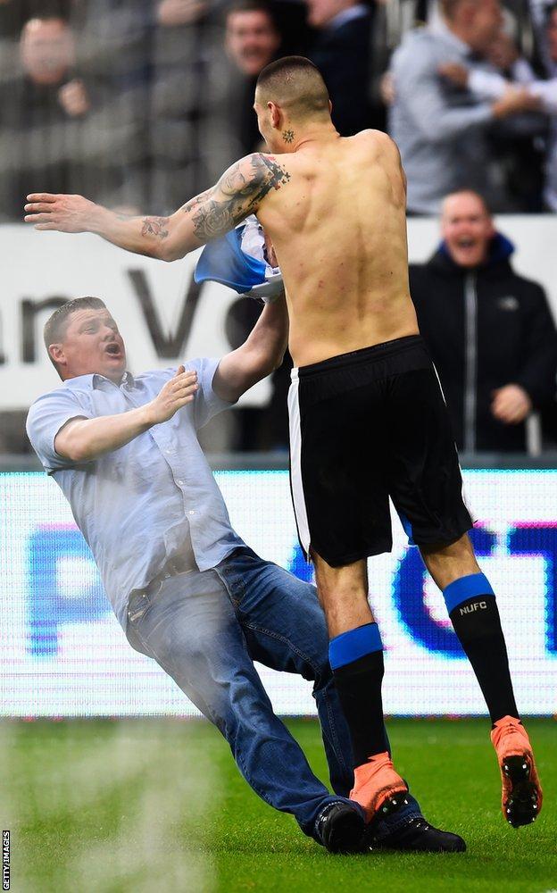 Aleksandar Mitrovic celebrates as a fan slips in front of him