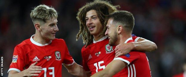David Brooks and Ethan Ampadu congratulate Aaron Ramsey who scored Wales' third goal