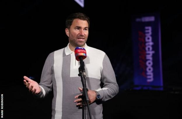 Eddie Hearn wearing a grey polo shirt with a white vertical stripe and a white blocked square