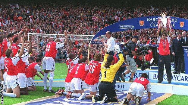 Robert Pires of Arsenal lifts the Premier League Trophy as his team mates kneel before him, May 2002
