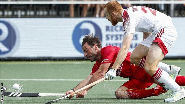 Belgium's Sebastien Dockier fights for the ball with England's Jack Waller