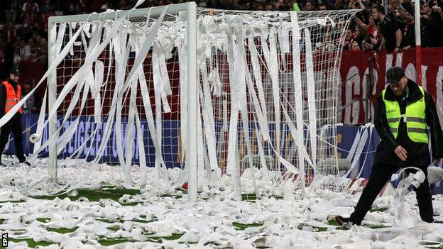 Security staff clear toilet roll from the pitch before the second half of Mainz against Freiburg