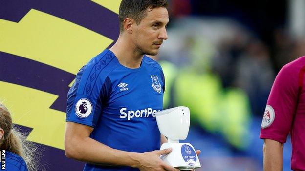 Everton captain Phil Jagielka carrying a robot mascot on to the pitch