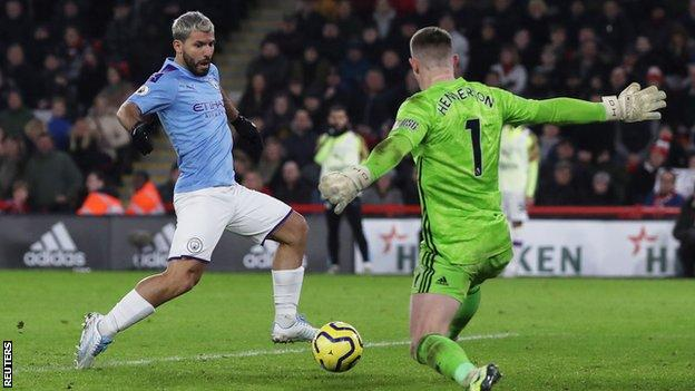 Manchester City striker Sergio Aguero taps past Sheffield United's Dean Henderson