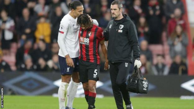 Nathan Ake being consoled by Virgil van Dijk as he leaves the field