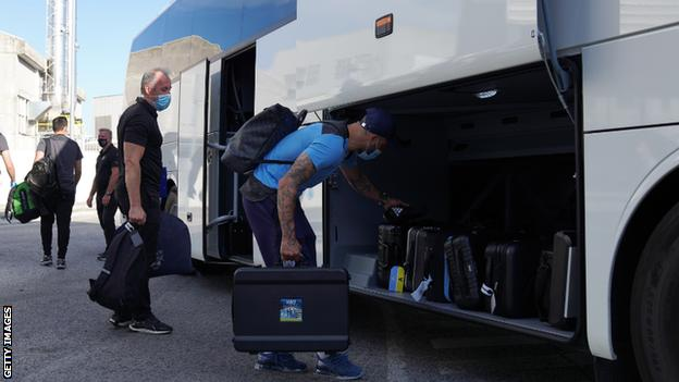 Manchester City's Kyle Walker collects his bag after arriving in Lisbon