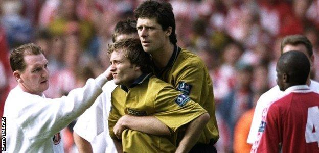 Sunderland striker Niall Quinn comforts Michael Gray after his penalty miss
