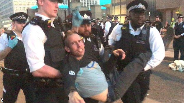 Etienne Stott is carried by police after being arrested
