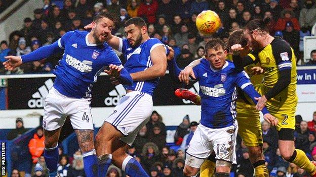 Ipswich and Burton players compete for a header