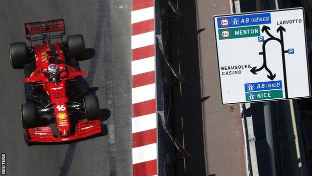 Charles Leclerc drives past a road sign