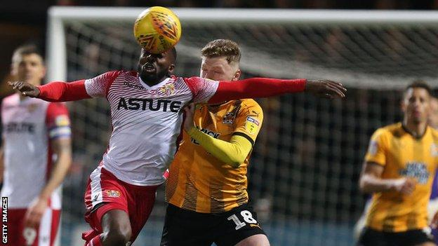 Stevenage's Emmanuel Sonupe get his head to the ball first