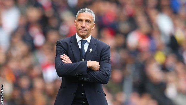 Chris Hughton stands with his arms folded