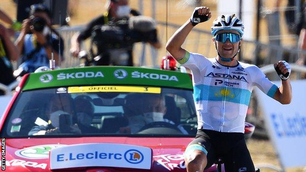 Alexey Lutsenko raises his arms in celebration after winning stage six of the 2020 Tour de France