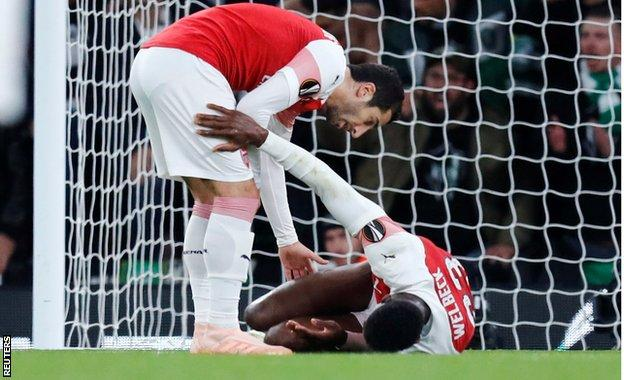 Arsenal's Henrikh Mkhitaryan with injured team-mate Danny Welbeck