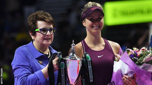 Elina Svitola is presented with the trophy by Billie Jean King