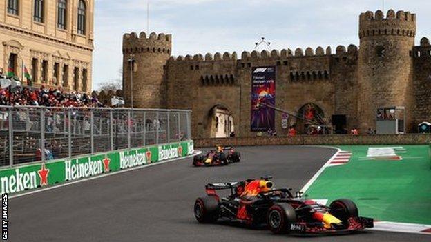 Max Verstappen and Daniel Ricciardo drive past the medieval castle in the city of Baku
