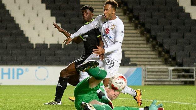 Bury goalkeeper Ben Williams saves from MK Dons striker Nicky Maynard