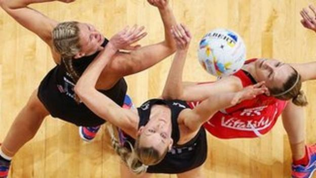 England and New Zealand netball players jump for the ball.