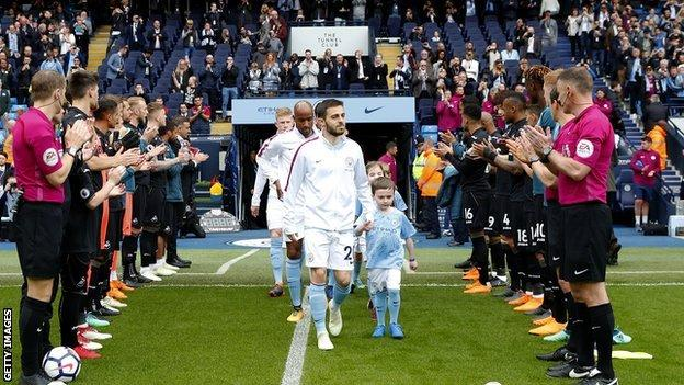Manchester City players walk out to a guard of honour