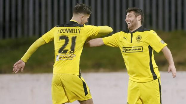 Jay Donnelly celebrates Cliftonville's second goal with scorer David McDaid who had earlier seen a penalty saved by Ryan Brown