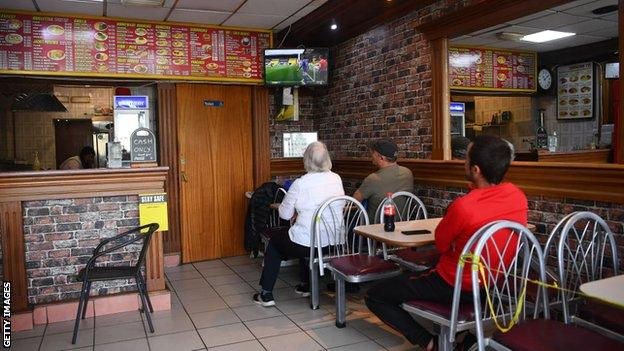 Fans watching the game in a cafe near Watford's stadium
