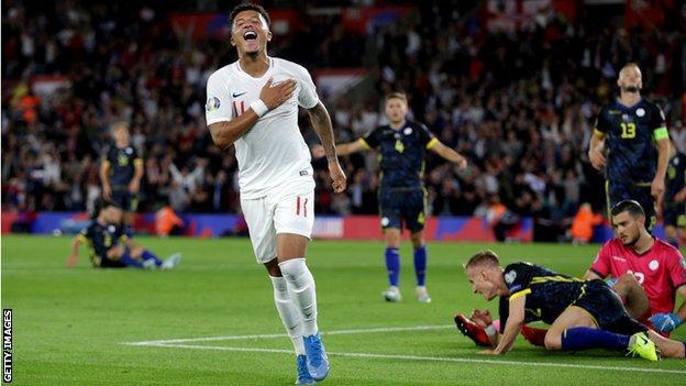 Jadon Sancho celebrates scoring for England