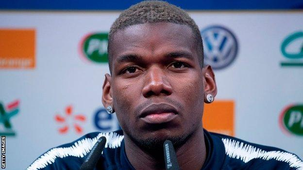 Paul Pogba told a news conference he remains happy at Manchester United