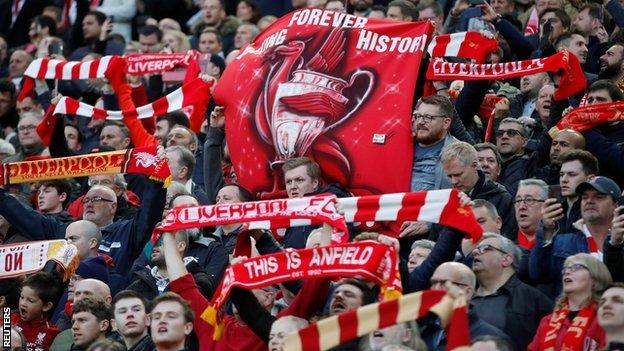 Celebrating Liverpool fans holding up scarves and banners