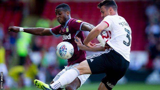 Aston Villa's Jonathan Kodjia battles with Sheffield United's Enda Stevens