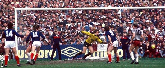 Albert Kidd (number 14) watches his shot fly past Hearts goalkeeper Henry Smith at a packed Dens Park