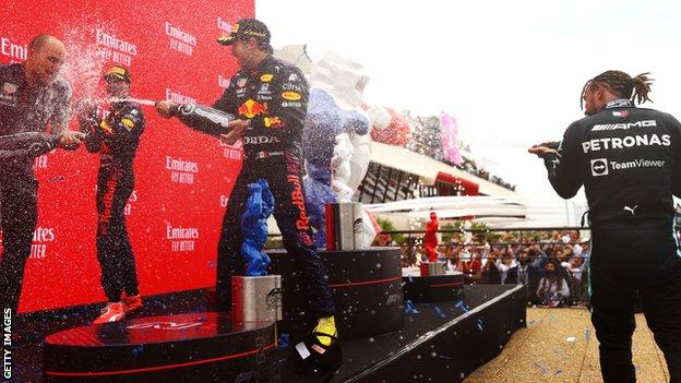 Lewis Hamilton, Max Verstappen and Sergio Perez engage in the champagne shower on the podium