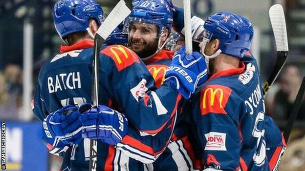 Great Britain ice hockey members celebrate a goal