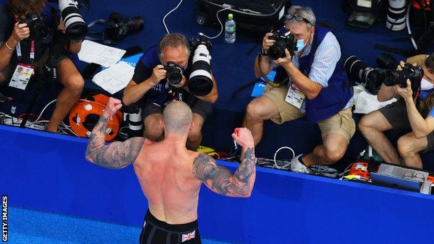 Adam Peaty poses in front of photographers after his gold medal-winning swim