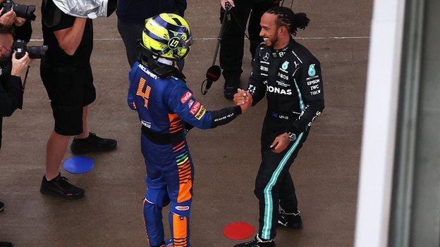 Lando Norris shakes hands with Lewis Hamilton