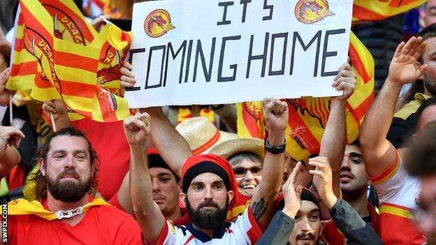 Catalans fan with an 'It's coming home' sign