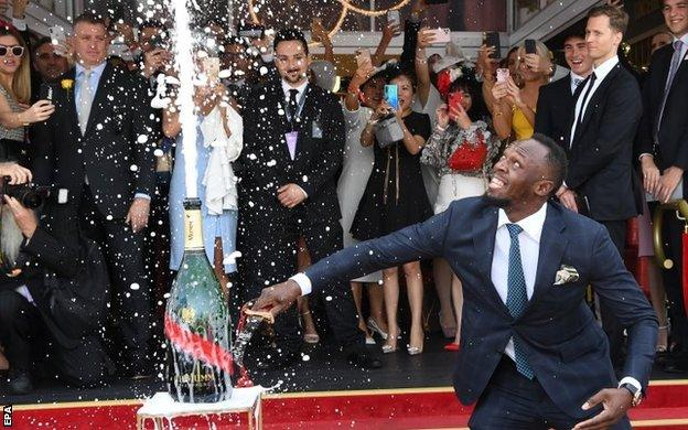 Usain Boltn opens a bottle of champagne at the Melbourne Cup