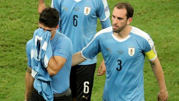 Diego Godin consoles Luis Suarez after Uruguay are knocked out of the Copa America