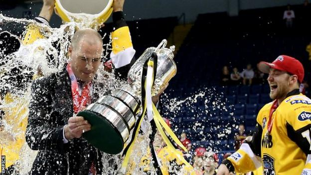 Corey Neilson has water thrown on him as he picks up the Elite League play-off trophy