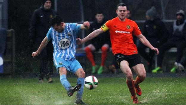 Warrenpoint Town's Conor McDoanld clears as Carrick's Aaron Harmon closes in
