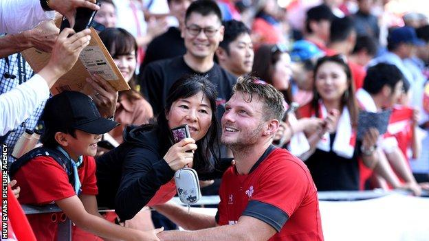 Wales rugby player Dan Biggar poses for a selfie with some of the 15,000 fans who turned up to watch the team train at Kitakyushu Stadium on 16 September