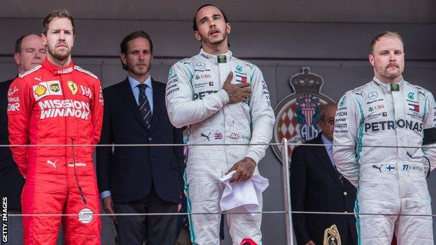 Lewis Hamilton stands on the podium