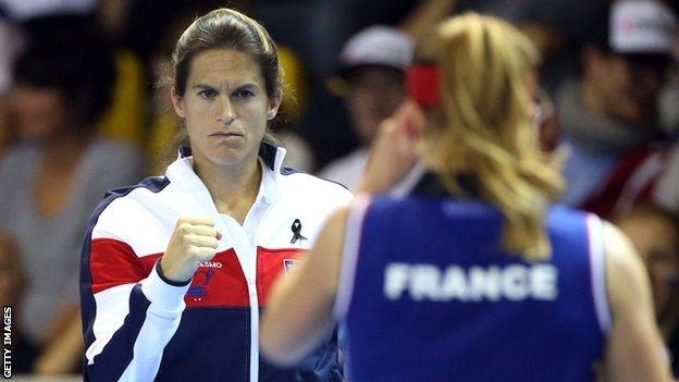 Amelie Mauresmo clenches her first in encouragement while France Fed Cup captain