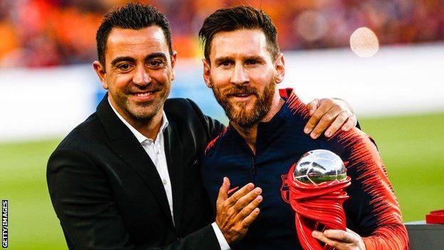 Xavi poses alongside Lionel Messi